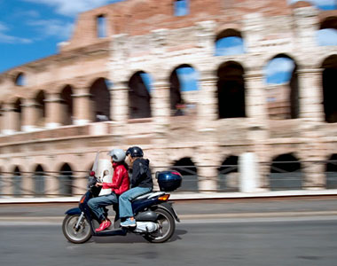 Riding a vespa in Rome